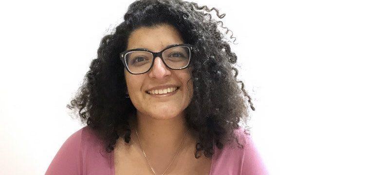 Imagen de Antonella sonriendo de frente, vestida con una camiseta rosada, pelo crespo suelto y usa lentes ópticos.